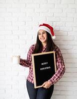 kvinna i tomtehatt med svart bokstavstavla foto