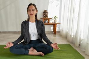 kvinna mediterar med händerna i gyan mudra position foto