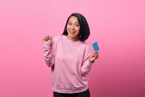 porträtt vacker ung asiatisk kvinna le med kreditkort foto