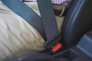 man tar på sig säkerhetsbältet i sin bil. säkerhetsdrivkoncept. foto