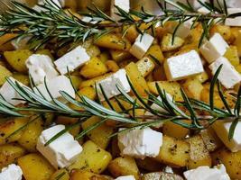 rostad rosmarinpotatis och fårost med örter och kryddor foto