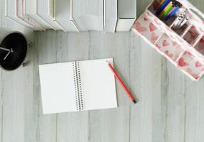 ett arbetsrum med en anteckningsbok pennor och klockor på det vita bordet. foto