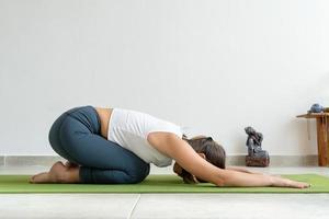 vacker kvinna utövar yoga asana balasana - på yogastudion foto