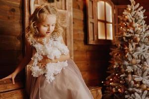 liten flicka i rosa klänning håller falsk snö foto