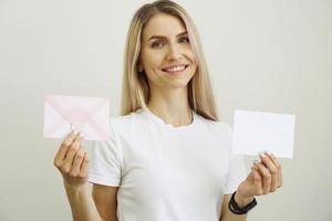 kvinna i vit t-shirt håller vitt tomt pappersark i handen foto