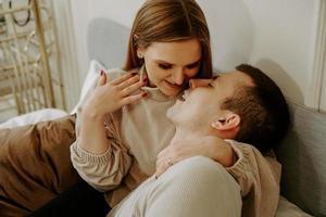 närbild porträtt av ett vackert ungt kyssande par i sängen hemma foto
