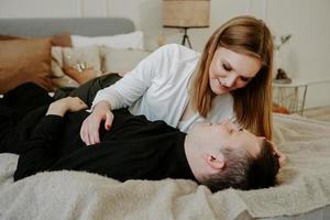 ganska kärleksfullt par i sängen tillsammans. de kramas och ler foto