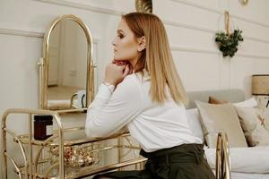vacker kvinna i hennes rum nära sitt toalettbord foto