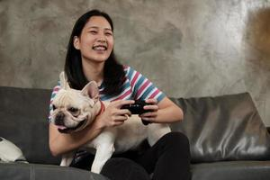 ung kvinna spelar spelkonsol med sin söta hund. foto