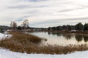 utsikt från flodens strand täckt med tunn is foto