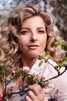 romantisk ung kvinna i vårträdgården bland äppelblom. foto