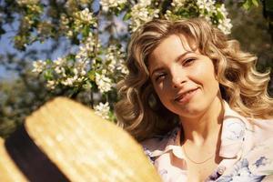 leende sommarkvinna med halmhatt i parken foto