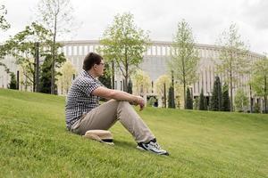 ung eftertänksam man som sitter på gräset i parken foto