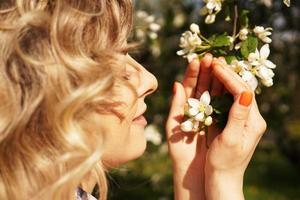 närbild av kvinnligt ansikte, kvinna som sniffar vita blommor foto