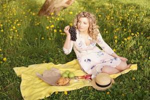 kvinna med druva på en picknick i sommarträdgården foto
