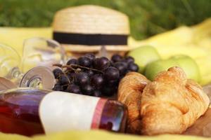 picknick på gräset med croissant, rosa vin, halmhatt, druva foto