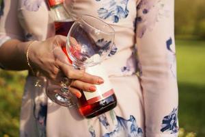 vacker ung kvinna som håller en tom flaska vin foto