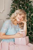 härlig ung kvinna med elegant stil med rosa julklapp foto