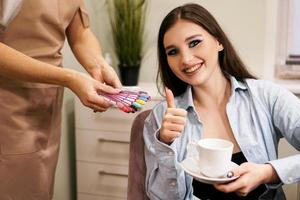 kvinna som visar tummen upp och ler i nagelsalongen foto