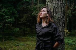 ung kvinna - nära porträtt i en mörk skog. kvinna i svart skjorta foto