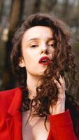 glamorös kvinna iklädd röd outfit och matchande rött läppglans. foto