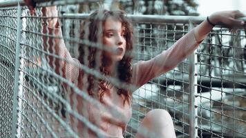 modeporträtt av trendig ung kvinna som sitter nära nätet rabitz foto