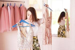 vacker kvinna som väljer kläder eller kläder i omklädningsrummet foto