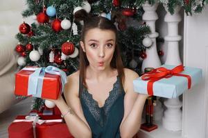 flicka i en grön peignoir som håller två presentförpackningar, vilken gåva att välja foto