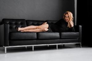 vacker tjej i svart klänning ligger på soffan foto