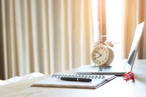 penna, anteckningsbok, glasögon och bärbar dator med väckarklocka på skrivbordet foto