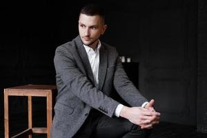 porträtt av en ung stilig elegant man på mörk bakgrund foto