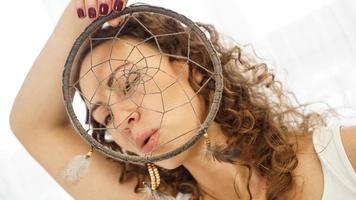 kvinna med lockigt hår med en drömfångare i handen foto