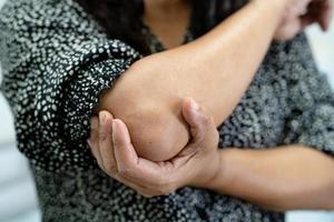 asiatisk kvinna patient beröring och känner smärta hennes armbåge och arm foto