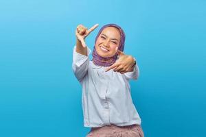 asiatisk kvinna tittar på kameran med händer som gör selfie foto