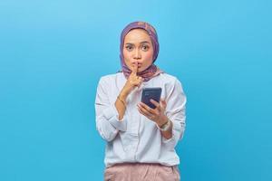 vacker asiatisk kvinna som håller smartphone och gör tyst gest foto