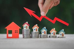 husmodell och en bunt mynt. fastighetsmarknaden, graf upp pil. begreppet inflation, ekonomisk tillväxt, fastighetsinvesteringar. foto