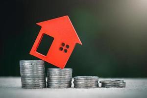 miniatyrfärgade hus på stackmynt, finans- och investeringskoncept och tillväxtintresse för fastigheter. foto