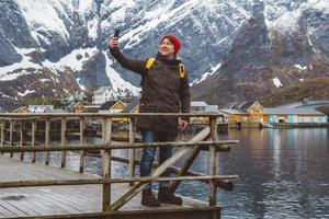 man tar selfie med berg och sjö bakom sig foto