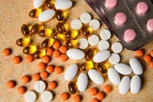 blister med rosa och apelsintabletter, vitamin D och fiskoljekapslar foto