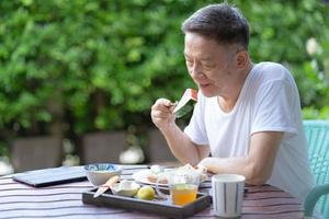 mogen man äter hälsosam frukost i trädgården foto