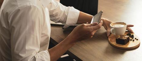 affärsman som använder smartphone för att ta foto av kaffe i café