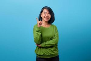 attraktiv asiatisk kvinna med leende och pekar upp med fingret foto
