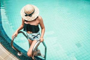 kvinna i baddräkt kopplar av i poolen foto