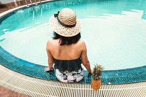 bakifrån av sexig kvinna i baddräkt avkopplande i poolen foto