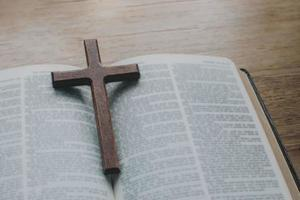 närbild av det enkla kristna korshalsbandet i trä på bibeln foto