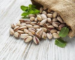 säck med pistagenötter på ett träbord foto