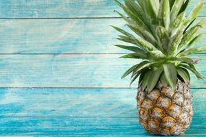 ananas med kopieringsutrymme på träbakgrund foto