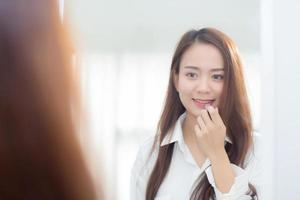 skönhet av porträtt av ung asiatisk kvinna vid spegeln som håller och tittar på ett läppstift för smink, vackert tjejskönhet på rummet, livsstilskoncept. foto