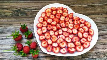 jordgubbar i en vit tallrik med ett hjärta. en romantisk servering foto