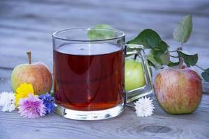 mugg med te bland frukter på en träbakgrund. foto